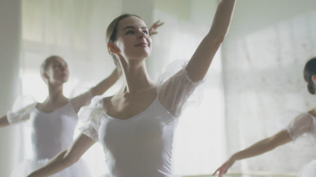 Mid Shot of Three Beautiful and Young Ballerinas Wearing White Tutus and Dancing. Shot Taking Place on a Sunny Morning in a Spacious and Bright Studio. In Slow Motion. video