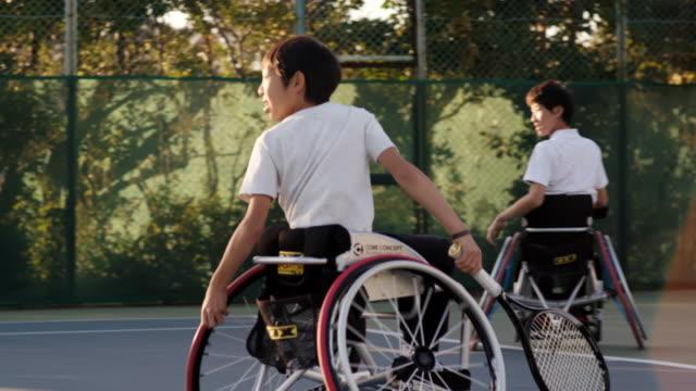 ダブルスをプレーする2人のアダプティブテニス選手のslo moミッドショット - disabilitycollection点の映像素材/bロール