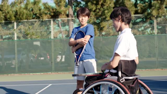 テニスコートで話している2人の友人のミッドショット - disabilitycollection点の映像素材/bロール