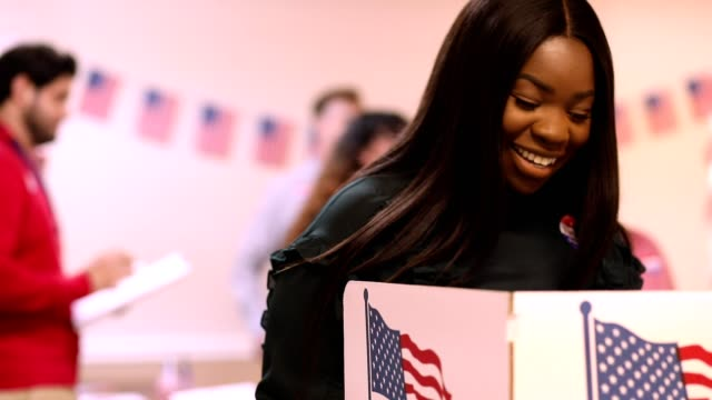 mid-adult, african descent woman votes in usa election. - vote filmów i materiałów b-roll
