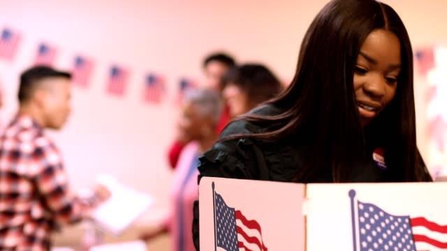Mid-adult, African descent woman votes in USA election. video