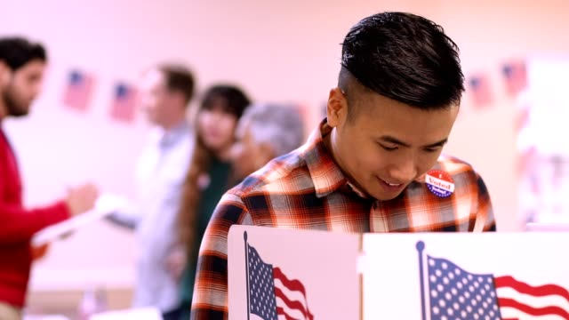 Mid-adult, Asian descent man votes in USA election. video