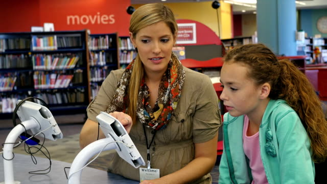Mid-adult Caucasian female librarian teaches elementary age student how to use check out equipment in library video