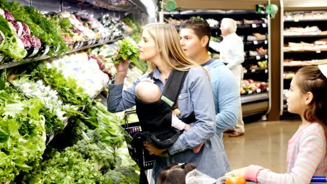 vídeos de stock, filmes e b-roll de mid-adulto caucasiana mãe e pai meados de adulto hispânica com três filhas jovens compras em supermercados locais - legume