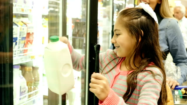 Mid-adult Caucasian mother is shopping with Hispanic elementary age daughter in dairy section at local grocery store video
