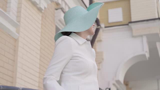 mitte-erwachsene kaukasische frau zu handläufen zu fuß und blickweg auf der stadtstraße. porträt von eleganten stilvollen glücklichen dame genießen sonnigen tag auf reisen. lifestyle, tourismus, freizeit, genuss. - einzelne frau über 30 stock-videos und b-roll-filmmaterial