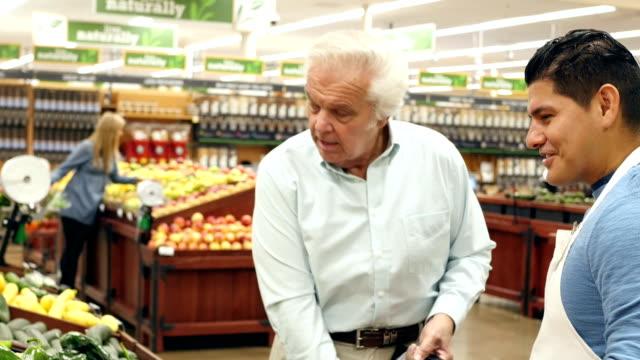 Mid-Adulto hispana supermercado empleado ayuda a senior hombre caucásico, de sexo masculino cliente seleccionado pimientos - vídeo