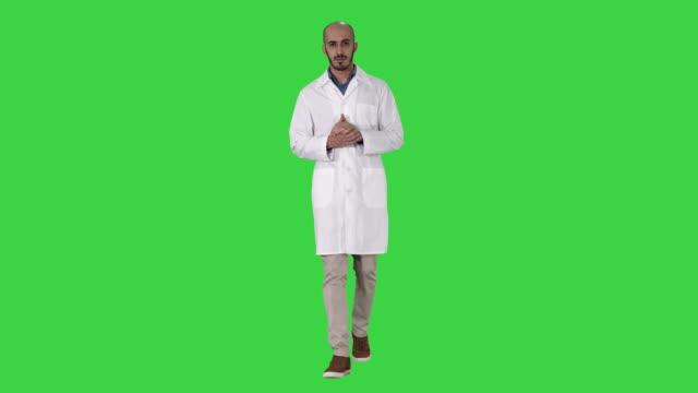 medico di mezza età che indossa un'uniforme medica che presenta e punta con un palmo della mano guardando la fotocamera su uno schermo verde, chroma key - braccio umano video stock e b–roll