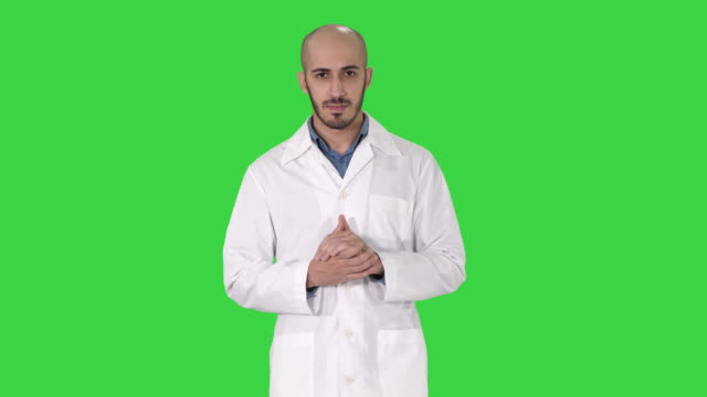 Middle age doctor man wearing medical uniform presenting and pointing with palm of hand looking at the camera on a Green Screen, Chroma Key