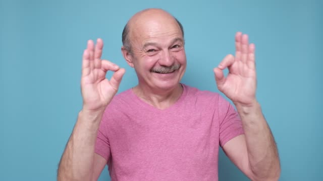 middle age man smiling positive doing ok sign approving choice. - znak ok filmów i materiałów b-roll