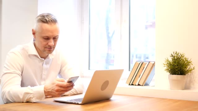 Middle Age Man Using Smartphone at Work video