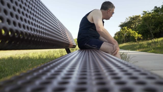 middle age man with knee pain on a park bench Middle aged Caucasian man with knee pain rests on a jogging path bench during outdoor exercise effort knee stock videos & royalty-free footage