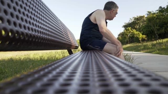 vídeos de stock e filmes b-roll de middle age man with knee pain on a park bench - dor
