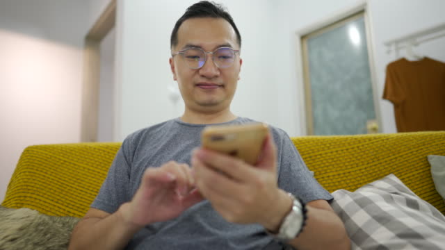 Middle age Taiwanese man using phone at home