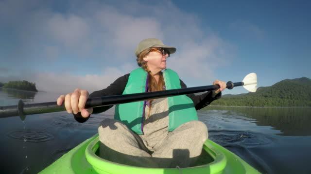 Middle age woman kayaking in a beautiful mountain lake