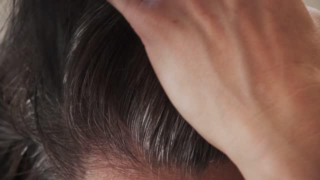 vidéos et rushes de femme d'âge moyen touchant ses cheveux foncés avec des cheveux gris aux racines des cheveux - gris