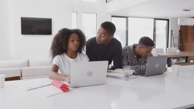 vídeos de stock e filmes b-roll de middle aged black dad helping his teen kids, doing their homework using laptops, front view - girl study home laptop front