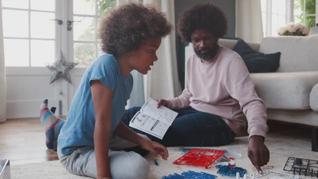 middle aged black father sitting on the floor at home helping his pre teen son with the instructions for a toy construction kit, close up, low angle - preadolescente video stock e b–roll
