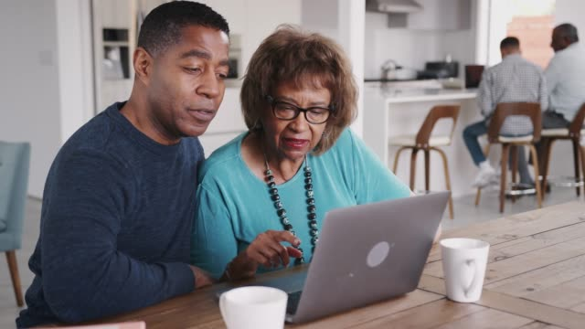 Middle aged black man helping his mother use a laptop computer at home, close up video