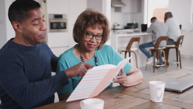 vídeos y material grabado en eventos de stock de hombre negro de mediana edad mirando a través de un álbum de fotos con su madre en casa, de cerca - memorial day