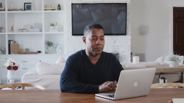 middle aged black man sitting at a table using laptop computer at home, close up, zoom in - usare il laptop video stock e b–roll