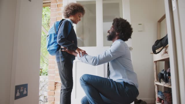 middle aged black man wearing a shirt and tie kneeling down preparing his son and saying goodbye before he leaves home for school in the morning, side view - отъезд стоковые видео и кадры b-roll