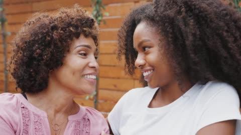 orta yaşlı siyah anne ve onun genç kızı konuşan ve birbirlerine gülümsüyor, yakın - kızlar stok videoları ve detay görüntü çekimi