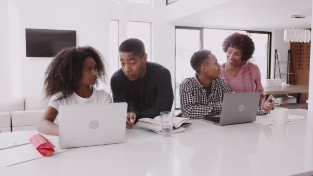 vídeos de stock e filmes b-roll de middle aged black parents helping their teenage kids, doing their homework using laptops - girl study home laptop front