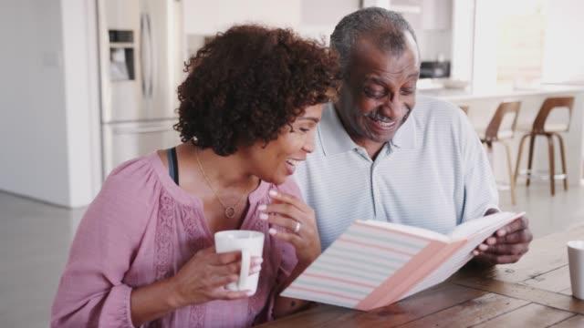 vídeos y material grabado en eventos de stock de mujer negra de mediana edad y su padre mirando a través del álbum de fotos juntos en casa, de cerca - memorial day