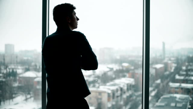 Middle aged businessman looking out a bright office window and thinking video