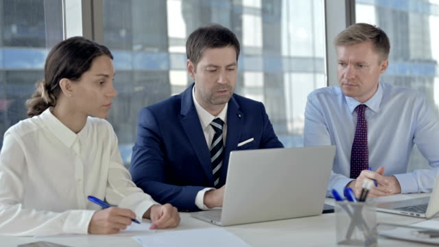 Middle Aged Businessman Sharing Report to his Assistants on his Laptop