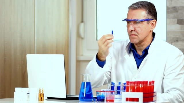 Middle Aged Chemist Analyzing Liquid in Test Tube video