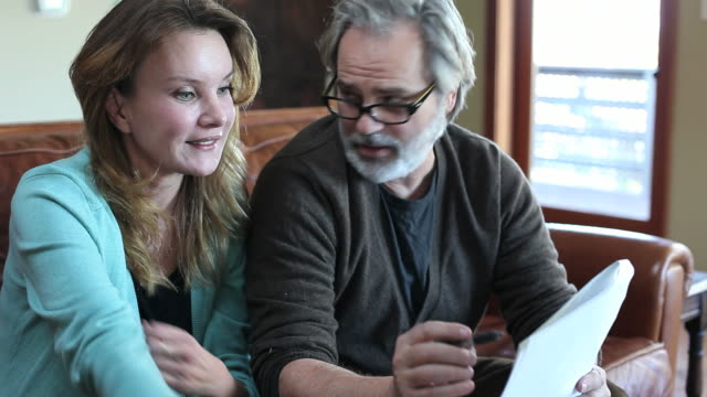 Middle aged couple reviewing documents video