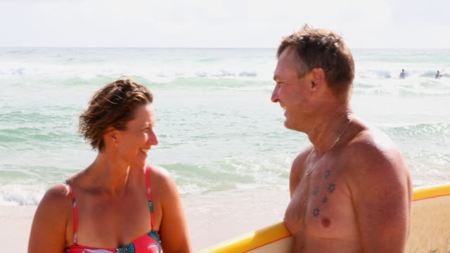 Middle Aged Couple With Malibu Longboard Surfboards Two Middle Aged People With Malibu Longboard Surfboards real life stock videos & royalty-free footage