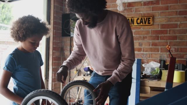 middle aged father and pre-teen son standing at a workbench building a racing kart together in their garage, close up, waist up - preadolescente video stock e b–roll