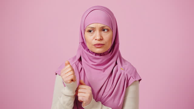 Middle aged islamic woman in pink hijab counting on fingers from one to five
