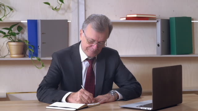 Middle aged leader writes note video