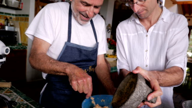 A middle aged man adds pepper to a dish while an elder shows him how it's done video