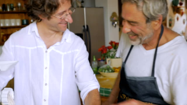 vídeos y material grabado en eventos de stock de un hombre de mediana edad y mayor se divierten trabajando juntos moliendo pescado - pascua judía
