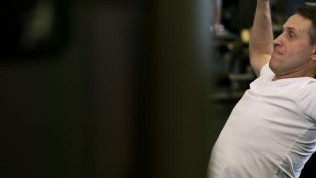 stockvideo's en b-roll-footage met middle aged man tillen halters - wit t shirt
