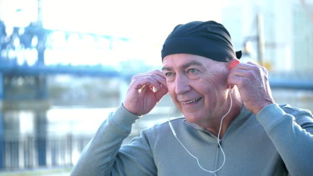 vídeos y material grabado en eventos de stock de hombre de mediana edad pone auriculares, canta a lo largo de la música - sudadera