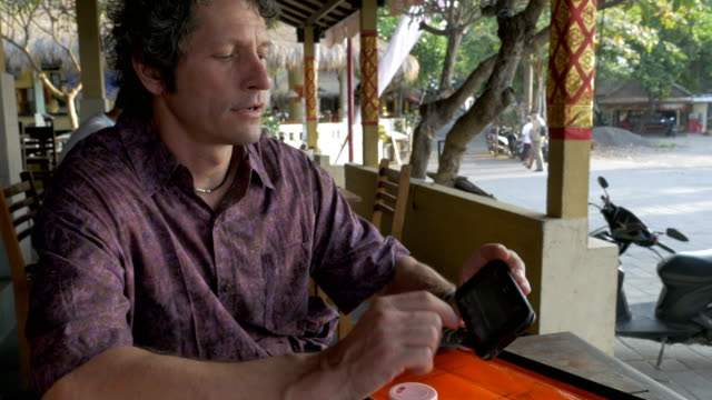 A middle aged man signs a form on a mobile cell phone in a cafe