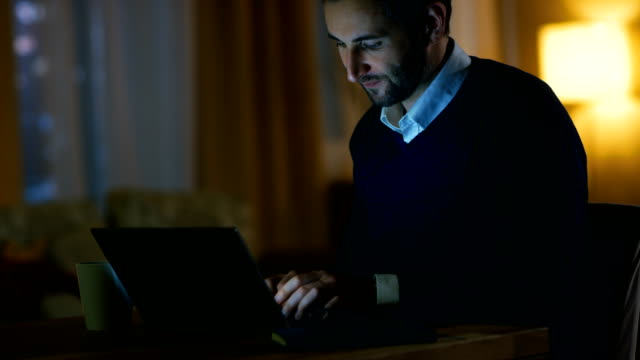 Middle Aged Man Sitting at His Desk Working on a Laptop. He's Satisfied.  He Smiles. In the Background His Apartment in Yellow Tones with a Skyscrapers View. video