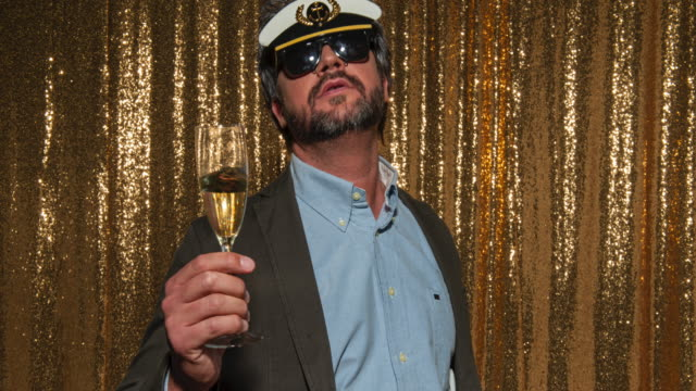 Middle aged man wearing a sailor hat and drinking wine while taking photos in the photo booth