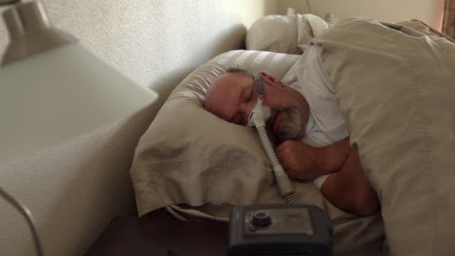 stockvideo's en b-roll-footage met middelbare leeftijd man met slaapapneu in slaap in een bed het dragen van een cpap (continue positieve luchtweg druk) machine om te helpen in zijn slaap - ventilator bed