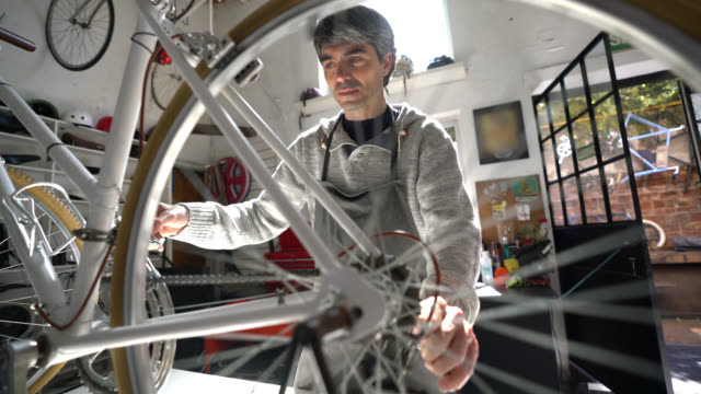 middle aged man working at a bicycle repair shop fixing a bicycle and spinning the back wheel looking very focused - warsztat filmów i materiałów b-roll