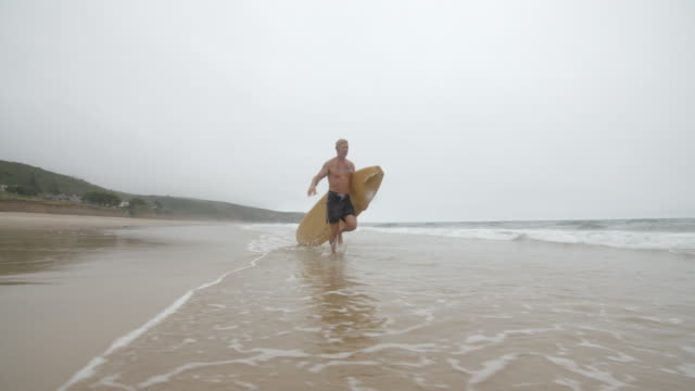 A middle aged surfer runs to the Ocean in Slow Motion. video