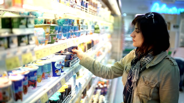 middle aged woman buys dairy products at a supermarket - prodotti supermercato video stock e b–roll