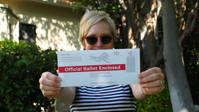 Middle Aged Woman Holds Up Her Vote By Mail Envelope A white woman hold up her vote by mail ballot in the envelop directly in front of her body. post office stock videos & royalty-free footage