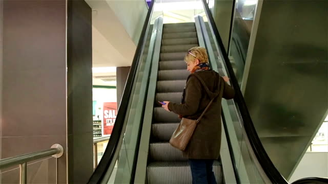 Middle aged woman on moving staircase in shopping mall video